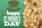 top view of golden shiny coins near happy st patricks day lettering on green background