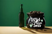 beer bottle and black pot with golden coins with irish lass full of sass lettering on green background