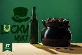 beer bottle and black pot with golden coins near lucky you lettering on green background