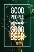 Fotografie pouring beer into glass with splash near good people drink good beer lettering on green background