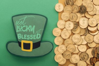 top view of golden coins near paper hat with not lucky just blessed lettering on green background