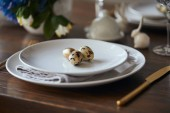 Photo selective focus of quail eggs on white plates and wooden table at home