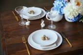 Fotografie Kristallglas, Blumen in Vase, goldene Besteck und dekorative Kaninchen auf Holztisch zu Hause