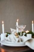 Selektivní fokus svíček a křišťálového skla na dřevěný stůl doma