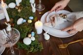 Fotografie Blick auf Frau weglegen Platten in der Nähe von brennenden Kerzen und Moos auf Holztisch zu Hause abgeschnitten