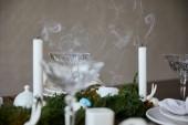 Selektivní fokus svíček u křišťálové skleničky a mechu na dřevěný stůl doma