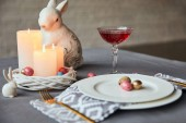 Photo selective focus of plates with napkin, eggs and burning candles in basket, wine in crystal glass and decorative rabbit on table at home
