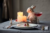 Photo selective focus of plates with eggs, wine in crystal glass, burning candles and decorative bunnies on table at home