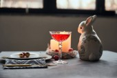 Photo selective focus of decorative bunnie, plates with eggs, wine in crystal glass, candles on table at home