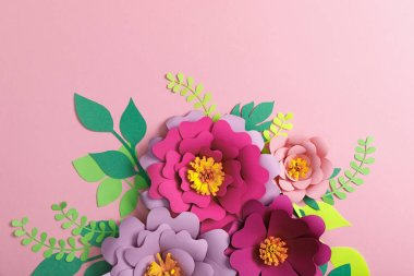 Top view of multicolored paper flowers and green leaves on pink background stock vector