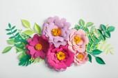 pohled shora růžové a lila papírové květy se zelenými listy na šedém pozadí