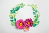 top view of pink paper flowers and leaves on grey background