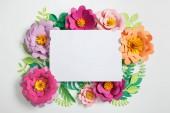 a különböző színű papír virágok, zöld levelek a szürke háttér fehér üres kártya felülnézet