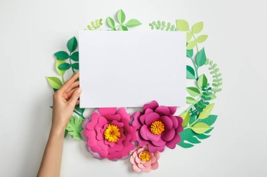 Cropped view of woman putting white blank card near pink paper flowers and leaves on grey background stock vector