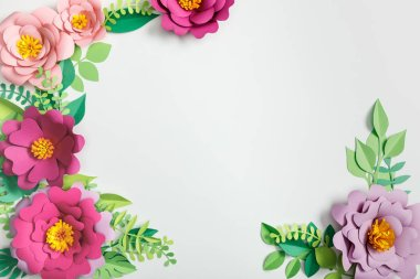 Top view of multicolored paper flowers and green plants with leaves on grey background stock vector