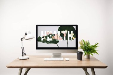 Computer with green leaves and health lettering on monitor on wooden desk stock vector