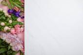 felülnézet gyönyörű friss rózsák, tulipánok és íriszek, rózsaszín és fehér háttér