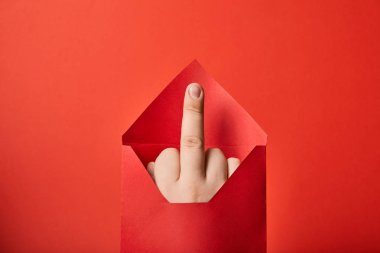 partial view of man showing middle finger in bright envelope on red background