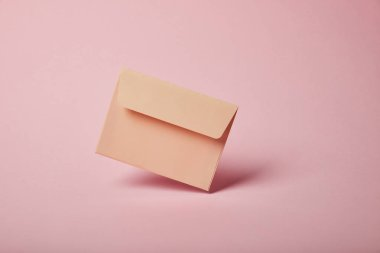 beige and empty envelope on pink background with copy space