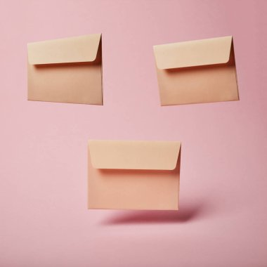 beige envelopes with copy space on pink and pastel background