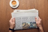 cropped view of man holding newspaper near cup of coffee
