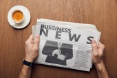 cropped view of man holding business newspaper near cup of coffee