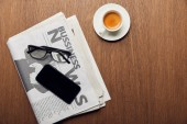 top view of newspaper near cup with coffee, smartphone with blank screen and glasses