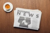 top view of business newspaper near cup with coffee