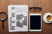 top view of magnifier near newspaper, cup with coffee, digital tablet with blank screen and glasses