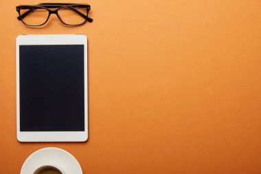 top view of digital tablet with blank screen near cup and glasses isolated on orange