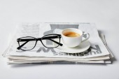 glasses near cup of coffee and business newspaper on white