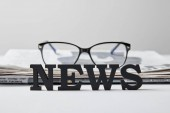 selective focus of news lettering near glasses and newspaper on white