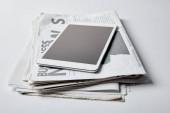 Digitální tablet s černou obrazovkou nedaleko obchodní noviny s články o bílé