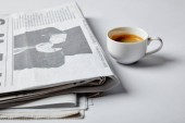 selective focus of cup with coffee near newspapers on white