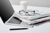 selective focus of laptop with blank screen near business newspapers,glasses, pen and paper cup on white