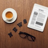 top view of digital tablet near news lettering, glasses and cup of coffee