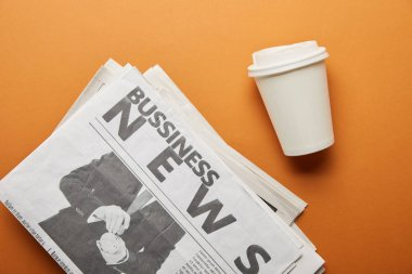 Top view of business newspaper near paper cup with drink on orange stock vector