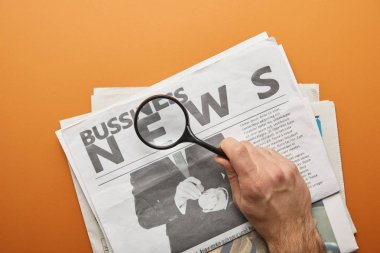 man holding magnifying glass and zooming news lettering while reading  business newspapers on orange