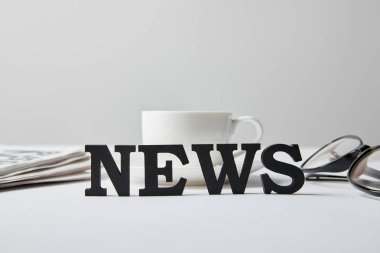 selective focus of news lettering near cup of coffee, glasses and newspaper on white