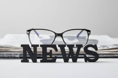 Selective focus of news lettering near glasses and newspaper on white stock vector