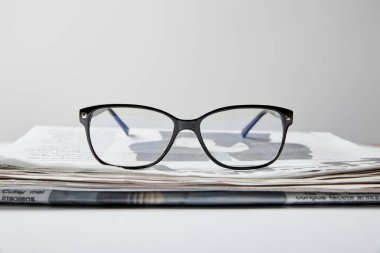 Selective focus of glasses near newspaper on white stock vector