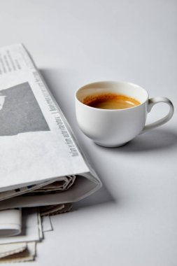 Selective focus of cup of coffee near newspapers on white stock vector