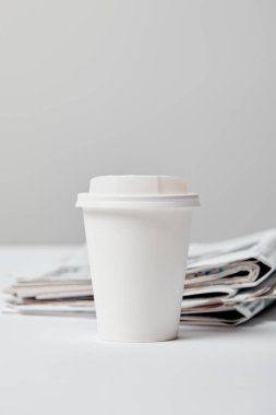 Selective focus of paper cup near newspapers on grey stock vector
