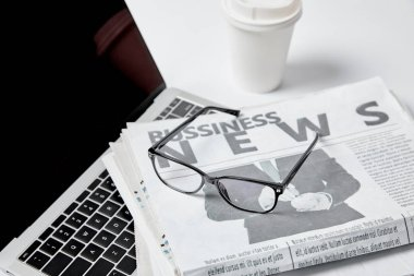 Laptop with blank screen near business newspapers, glasses, paper cup and pen on white stock vector