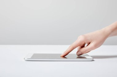 cropped view of woman using digital tablet on white