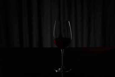 Silhouette of glass with burgundy red wine on dark