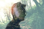 Double exposure of man in glasses and green forest