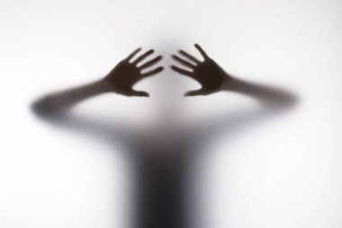 Blurry silhouette of person touching glass with hands stock vector