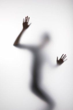 Blurry silhouette of person touching glass with hands