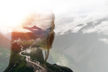 Double exposure of girl and mountains in clouds